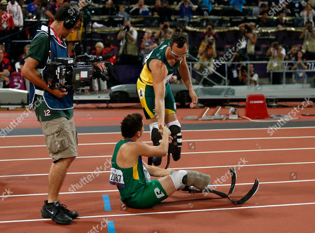 Gold medalist South Africa's Oscar Pistorius, top, shakes hands with fourth place finisher Brazil's Alan Oliveira after they ran in the men's 400 meters T44 category final during the athletics competition at the 2012 Paralympics, in London