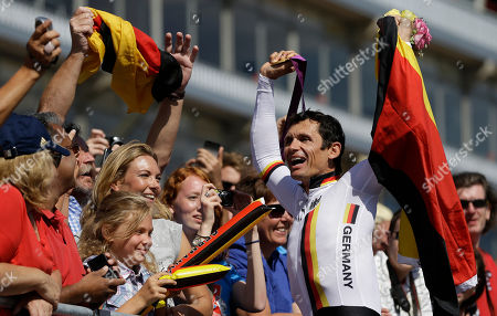 Michael Teuber of Germany holds up the national flag of Germany as he goes to embrace his wife Susanne, fourth left, and daughter Marieann, third left, as he celebrates with his gold medal following the medal ceremony for the men's road cycling individual time trial C1 category at the 2012 Paralympics games, at Brands Hatch motor racing circuit near London