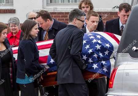 Family members place the casket of former Democratic U.S. Senator and three-time presidential candidate George McGovern onto a hearse as it is being transported to the Washington Pavilion of Arts and Science in Sioux Falls, S.D., for the funeral service, . McGovern died Sunday in his native South Dakota at age 90