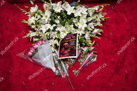 A picture of Mexican singer Chavela Vargas sits on bouquets next to the casket, not seen, during her wake in Bellas Artes Palace in Mexico City, . Chavela Vargas, who defied gender stereotypes to become one of the most legendary singers in Mexico, died Aug. 5 at age 93