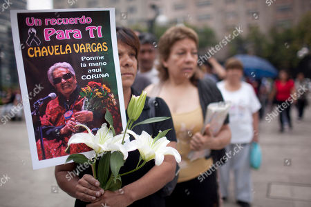 A woman holds a bouquet and a picture of late Mexican singer Chavela Vargas before attending her wake in Mexico City, . Chavela Vargas, who defied gender stereotypes to become one of the most legendary singers in Mexico, died Aug. 5 at age 93