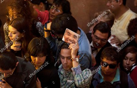 A man holds up a compact disc of late Mexican singer Chavela Vargas during her wake in Bellas Artes Palace in Mexico City, . Chavela Vargas, who defied gender stereotypes to become one of the most legendary singers in Mexico, died Aug. 5 at age 93