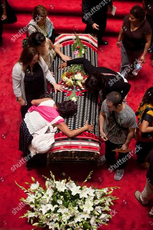 People mourn next to the draped casket of the late Mexican singer Chavela Vargas during her wake in Bellas Artes Palace in Mexico City, . Chavela Vargas, who defied gender stereotypes to become one of the most legendary singers in Mexico, died Aug. 5 at age 93