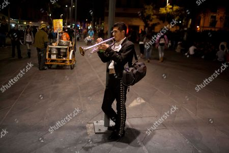 Photo, professor at the Mariachi School Ollin Yoliztli, Eduardo Sanchez Ortiz, practices as he waits for clients at Plaza Garibaldi in Mexico City. The new mariachi school in Mexico City is seeking to revive a music that's lost ground over the years. The school, whose name means life and movement in indigenous Nahautl, teaches folk bands how to play professionally while grooming a new generation of songwriters and composers