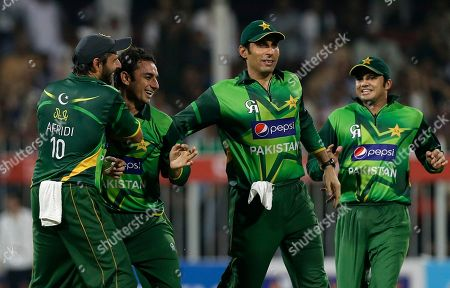 Pakistan's bowler Saeed Ajmal, second left, celebrates with his teammates taking the wicket of Australia's David Hussey, not pictured, during the third cricket ODI match of a three match series between Australia and Pakistan, at Sharjah Cricket Stadium, in Sharjah, United Arab Emirates