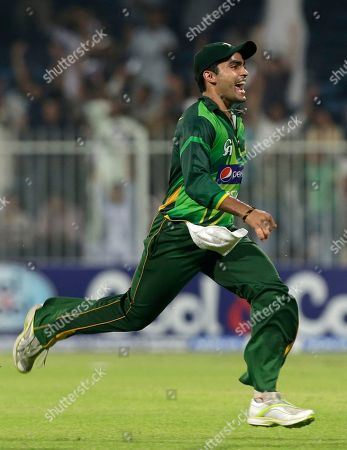 Pakistan's Kamran Akmal celebrates as his teammate bowler Saeed Ajmal, not pictured, taking the wicket of Australia's David Hussey, not pictured, during the third cricket ODI match of a three match series between Australia and Pakistan, at Sharjah Cricket Stadium, in Sharjah, United Arab Emirates