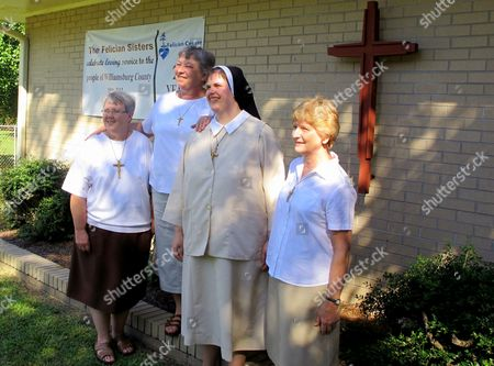Stock Photo of Felician sisters who have been honored with the national Light of Christ award from Catholic Extension for their work in rural South Carolina pose outside their center in Kingstree, S.C.,on Tuesday, Sept.11, 2012. The sisters are, from left, Sister Mary Johnna Ciezobka, Sister Mary Susanne Dziedzic, Sister Heather Marie Deneen and Sister Mary Jacqueline Benbenek