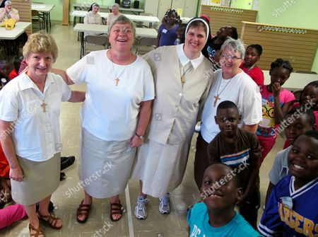 Stock Image of Felician sisters who have been honored with the national Light of Christ award from Catholic Extension for their work in rural South Carolina pose inside their center in Kingstree, S.C., with students in their after school program on . The sisters are, from left, Sister Mary Jacqueline Benbenek, Sister Mary Susanne Dziedzic, Sister Heather Marie Deneen and Sister Mary Johnna Ciezobka