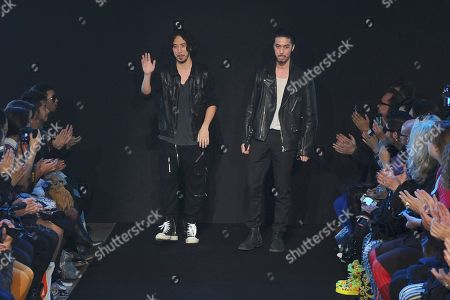 British fashion designers and brothers Eri, left, and Philip Chu acknowledge applauses after the presentation for Ground Zero fashion house's ready to wear Spring-Summer 2013,in Paris, Sunday, Sept.30, 2012