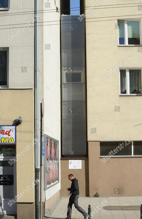 """A passerby walks past one of the world's narrowest houses, in Warsaw, Poland, . The two-level """"Keret's House"""" is no wider than 122 centimeters (48.03 inches) and was fitted into tiny space puzzlingly left between a pre-war house and a modern apartment block of the 1960s in downtown Warsaw. It is named after Etgar Keret, an Israeli writer of Polish roots who will be the first inhabitant of this artistic project of aluminum and polycarbonate"""