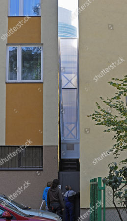 """Workers adjust a gate in front of one of the world's narrowest houses, in Warsaw, Poland, . The two-level """"Keret's House"""" is no wider than 122 centimeters (48.03 inches) and was fitted into tiny space puzzlingly left between a pre-war house and a modern apartment block of the 1960s in downtown Warsaw. It is named after Etgar Keret, an Israeli writer of Polish roots who will be the first inhabitant of this artistic project of aluminum and polycarbonate"""