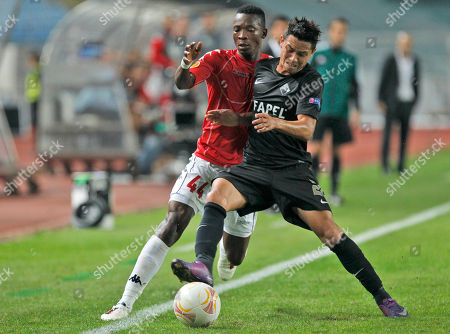 Hapoel Tel Aviv's John Pantsil, left, from Ghana, duels for the ball with Academica's Cleyton, from Brazil, during their Europa League group B soccer match at the Cidade de Coimbra stadium, in Coimbra, Portugal