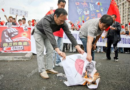 Stock Photo of Members of the Chinese community in Romania burn a paper with the Japanese flag printed on along with a picture of the Japanese Emperor Akihito during a protest in Bucharest, Romania, Tuesday, Sept.18, 2012. China's national defense minister, Gen. Liang Guanglie, warned Tuesday that Beijing reserves the right to take further action against Japan in the ongoing dispute over uninhabited islands in the East China Sea.Tensions over the string of islands, called the Senkakus in Japan and Diaoyu in China, spiked last week when the Japanese government said it was purchasing some of the islands from their private owner