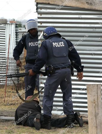 South African police officers search a man as they patrol the area near the Lonmin Platinum Mine near Rustenburg, South Africa, . As various stakeholders continued negotiations South Africa's Justice Minister Jeff Radebe warned that the Government would clamp down on daily illegal marches by miners brandishing machetes, spears and clubs that have marked the strike