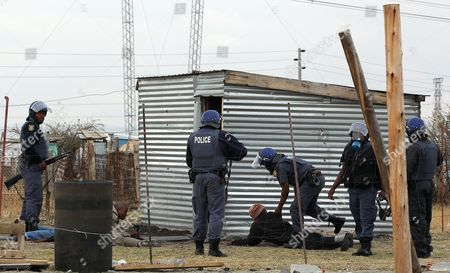 Police officers round up a group of men as they patrol the area near the Lonmin Platinum Mine near Rustenburg, South Africa, . As various stakeholders continued negotiations South Africa Justice Minister Jeff Radebe warned that the Government would clamp down on daily illegal marches by miners brandishing machetes, spears and clubs that have marked the strike