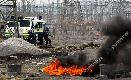 Police arrive as residents burning tires in Lonmin Platinum Mine near Rustenburg, South Africa, . As various stakeholders continued negotiations, South African Justice Minister Jeff Radebe warned that the Government would clamp down on daily illegal marches by miners brandishing machetes, spears and clubs that have marked the strike