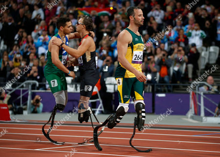Gold medal winner Brazil's Alan Fonteles Cardoso Oliveira, left, embraces Germany's David Behre, center, as silver medalist South Africa's Oscar Pistorius walks away after they ran the men's 200m T44 category final during the athletics competition at the 2012 Paralympics. Pistorius is beaten in the final of the 200 meters by Brazil's Alan Oliveira, a major surprise, and then complains about the length of Oliveira's running blades. For the first time, public opinion appears to be against Pistorius as fans label him a sore loser
