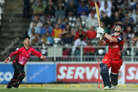 Highveld Lions's batsman Chris Morris, right, watches his midair shot as Sydney Sixers captain Brad Haddin, left, runs to take a catch during the final of their Champions League Twenty20 cricket match at the Wanderers Stadium in Johannesburg, South Africa