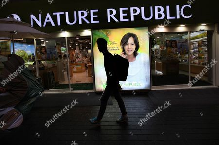 """A man walks by an advertisement featuring Jang Keun-suk, a South Korean celebrity often given the title """"flower man"""" by news media in Seoul, South Korea. The metamorphosis of South Korean men from macho to makeup over the last decade or so can be partly explained by fierce competition for jobs, advancement and romance in a society where, as a popular catchphrase puts it, """"appearance is power"""