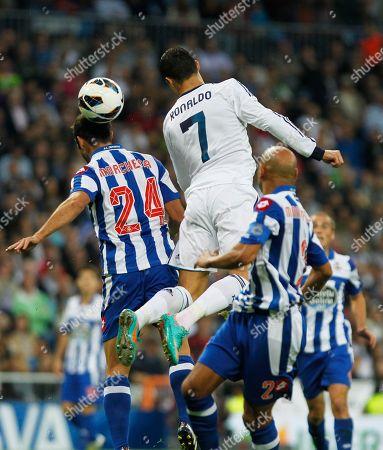 Cristiano Ronaldo, Carlos Marchena Real Madrid's Cristiano Ronaldo from Portugal, centre, in action with Deportivo la Coruna's Carlos Marchena, right, during a Spanish La Liga soccer match at the Santiago Bernabeu stadium in Madrid, Spain