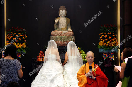 You Ya-ting, left, and her partner Huang Mei-yu kneel in front of a statue of Buddha in the prayer hall as they are married in the first Taiwan same sex Buddhist ceremonial wedding in Taoyuan, Taiwan, . Taiwan still does not legally recognize same sex marriage