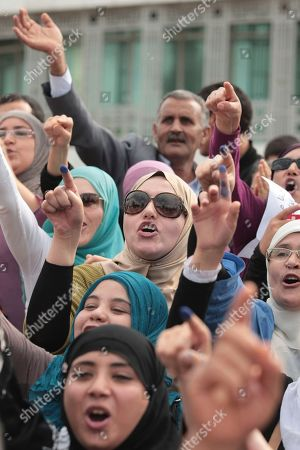 Stock Picture of Pro-government demonstrators, among them, Soumaya Gannouchi, center with sunglasses, the daughter of Rached Ghannouchi, leader of the Ennahdha party, shout, during a protest in Tunis, as Tunisia marks the turbulent and tense anniversary of the first elections since the fall of its totalitarian leader. Tensions are on the rise in Tunisia on the anniversary of the country's first post-Arab Spring elections, with both radical Islamists and political leaders warning of a high security risk as thousands are expected to march in support of the young government