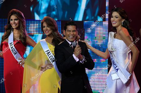 Miss Aragua Elian Herrera, left, Miss Falcon Alyz Henrich, second from left, journalist Ismael Cala, second from right, and Miss Guarico Maria Gabriela Isler smile during the Miss Venezuela 2012 beauty contest in Caracas, Venezuela
