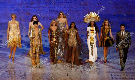 Stock Picture of Models, from left, Lily Cole, Karen Elson, Stella Tennant, Kate Moss, Lily Donaldson, Naomi Campbell, Jourdan Dunn and Georgia May Jagger walking with a male model during the Closing Ceremony at the 2012 Summer Olympics in London. Gold was the new black at the closing ceremony with a parade of supermodels wearing gilded gowns in a tribute to British fashion. Kate Moss and Naomi Campbell both had on Alexander McQueen, Georgia May Jagger's was by Victoria Beckham, Karen Elson was in Burberry, and Stella Tennant donned a Christopher Kane Swarovski-crystal catsuit
