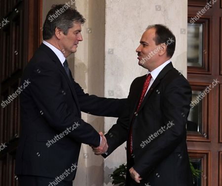 Albania's new President Bujar Nishani, right, shakes hands with outgoing President Bamir Topi after he was sworn in at a parliament session to become post-communist Albania's sixth president, in Tirana