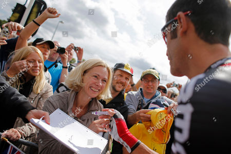 George Hincapie of the US signs autographs prior to the start of the first stage of the Tour de France cycling race over 198 kilometers (123 miles) with start in Liege and finish in Seraing, Belgium, . Hincapie, who is riding his 17th Tour de France, came over to sign autographs after a cycling fan, cneter, waved the US flag to get his attention