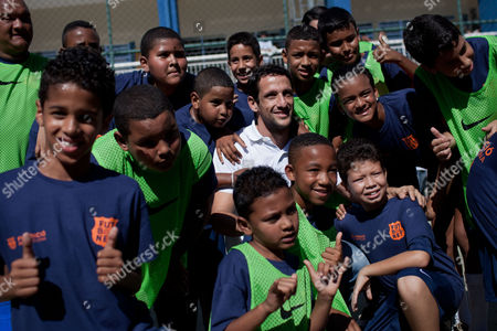 Former Barcelona player Juliano Belletti, from Brazil, pose with children of the Futbol Net project at the Complexo do Alemao slum in Rio de Janeiro, Brazil, . Rio de Janeiro City Hall and Barcelona Foundation launched the Futbol Net project, a sport and social development program at the Olympic Village in the Complexo do Alemao slum