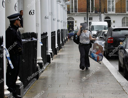 A Police investigation officer, sheltering from the rain with a folder, arrives at the home of Britain's richest women, American-born Eva Rausing who was found dead in her home in Belgravia, London, . American-born Eva Rausing, was found dead in her west London home and a man was arrested in connection with the case, British police said, adding that an autopsy had failed to uncover a formal cause of death