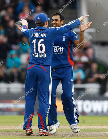 England's Ravi Bopara, right, celebrates with teammate Eoin Morgan after taking the wicket of Australia's David Hussey for 9 during their One Day International cricket match at Old Trafford cricket ground, Manchester, England