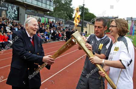 Stock Picture of The Olympic Flame is passed between Sir Roger Bannister and Oxford doctoral student Nicola Byrom on the running track at Iffley Road Stadium in Oxford, England, . Bannister was the first person ever to run a sub four-minute-mile, on May 6, 1954, at this track in Oxford. Bannister returned to the site of his greatest sporting achievement, to participate in the Olympic Torch relay as the Olympic flame is carried around the country to the opening ceremony of the 2012 London Olympic Games