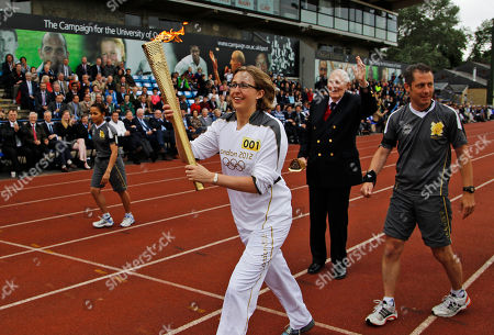 Stock Photo of Oxford University doctoral student Nicola Byrom carries the Olympic Flame after it was passed from Sir Roger Bannister, 2nd right waving, on the running track at Iffley Road Stadium in Oxford, England, . Bannister was the first person ever to run a sub four-minute-mile, on May 6, 1954, at this track in Oxford. Bannister returned to the site of his greatest sporting achievement, to participate in the Olympic Torch relay as the Olympic flame is carried around the country to the opening ceremony of the 2012 London Olympic Games