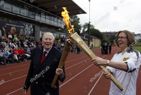 The Olympic Flame is passed between Sir Roger Bannister and Oxford doctoral student Nicola Byrom on the running track at Iffley Road Stadium in Oxford, England, . Bannister was the first person ever to run a sub four-minute-mile, on May 6, 1954, at this track in Oxford. Bannister returned to the site of his greatest sporting achievement, to participate in the Olympic Torch relay as the Olympic flame is carried around the country to the opening ceremony of the 2012 London Olympic Games