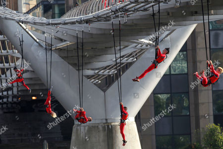 """Extreme dancers perform, hanging from the Millennium Bridge in London during London 2012 Olympic Festival, . The performance """"Surprises :Streb,"""" choreographed by New Yorker Elizabeth Streb, takes place on various London's landmarks"""