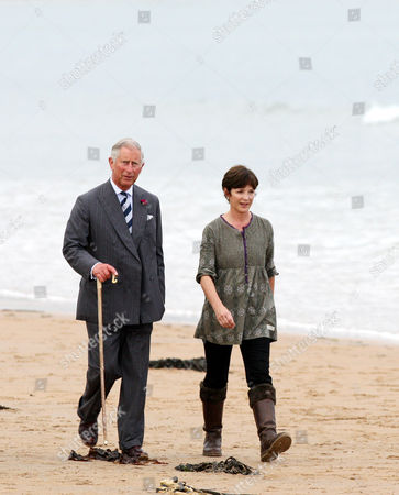 Britain's Prince Charles, left, and the Duchess of Northumberland are seen walking along the beach at Dunstan Steads, Dunstan, England
