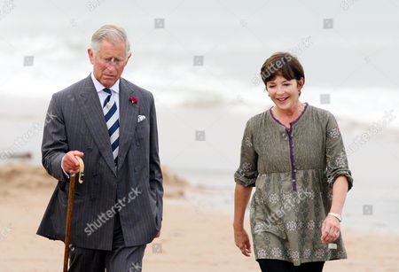 Stock Picture of Britain's Prince Charles, left, and the Duchess of Northumberland are seen walking along the beach at Dunstan Steads, Dunstan, England