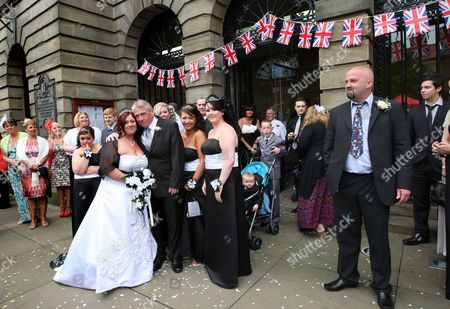 Newly married bride Vee Curry and her husband David Curry pose outside the town hall in Morpeth, England, decorated with Jubilee bunting, following their wedding ceremony. The bride said it was 'fitting' to be married on the day the Queen celebrated her Diamond Jubilee. Britain is marking Queen Elizabeth II's 60 years on the throne with a four-day holiday weekend of ceremony, symbolism and street parties. AP Photo/Scott Heppell