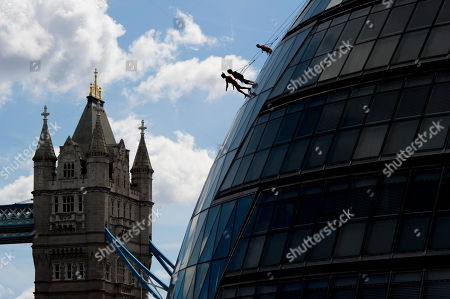 Streb Artists from performance company STREB, founded by Elizabeth Streb, perform an acrobatic abseil down City Hall, London
