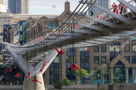 Streb Artists using trapezes and bungee ropes from performance company STREB, founded by Elizabeth Streb, perform acrobatics from the Millennium Bridge, London