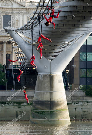 Stock Photo of Streb Artists using trapezes and bungee ropes from performance company STREB, founded by Elizabeth Streb, perform acrobatics from the Millennium Bridge, London