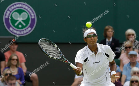 Akgul Amanmuradova of Uzbekistan returns a shot to Petra Kvitova of the Czech Republic during a first round women's singles match at the All England Lawn Tennis Championships at Wimbledon, England