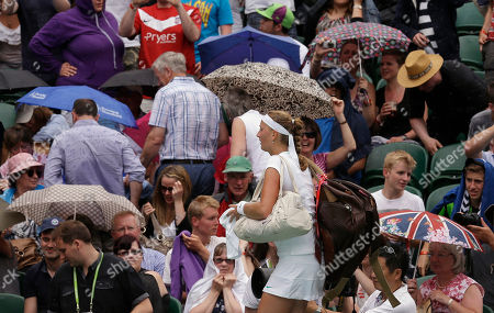 Petra Kvitova of the Czech Republic walks off the court as rain delays play in a first round women's singles match against Akgul Amanmuradova of Uzbekistan at the All England Lawn Tennis Championships at Wimbledon, England