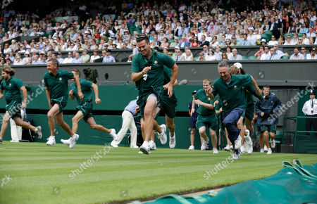 Ground staff run onto the court to place the covers as rain halts play between Petra Kvitova of the Czech Republic Akgul Amanmuradova of Uzbekistan during a first round women's singles match at the All England Lawn Tennis Championships at Wimbledon, England