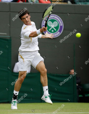 Jamie Baker of Britain returns a shot to Andy Roddick of the United States during a first round men's singles match at the All England Lawn Tennis Championships at Wimbledon, England