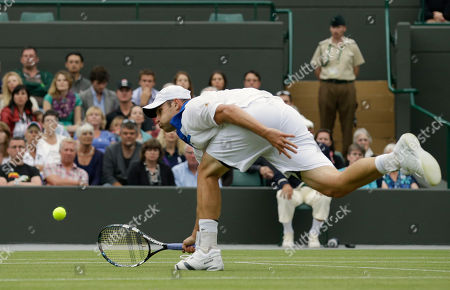 Andy Roddick of the United States plays a shot to Jamie Baker of Britain during a first round men's singles match at the All England Lawn Tennis Championships at Wimbledon, England