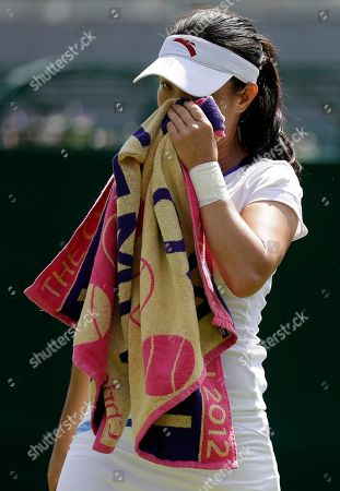 Zheng Jie of China wipes her face during a first round women's singles match against Stephanie Dubois of Canada at the All England Lawn Tennis Championships at Wimbledon, England