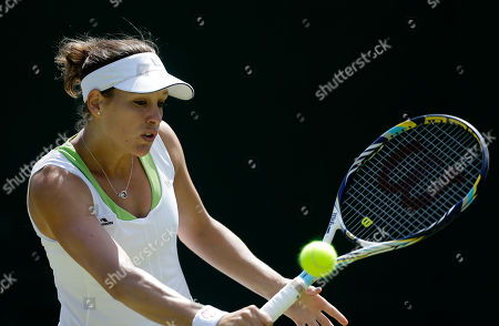 Stephanie Dubois of Canada returns a shot to Zheng Jie of China during a first round women's singles match at the All England Lawn Tennis Championships at Wimbledon, England